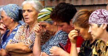 Women wait for news from the school seized by attackers in North Ossetia