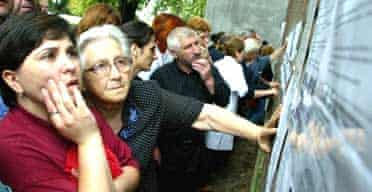 Ossetians search for loved ones on a hostage list at Beslan's hospital