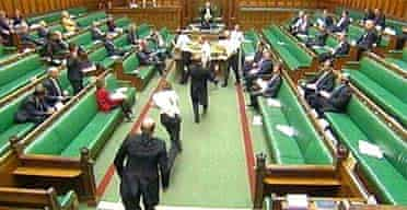 Protesters in white T-shirts, pursued by guards after they got onto the floor of the Commons chamber