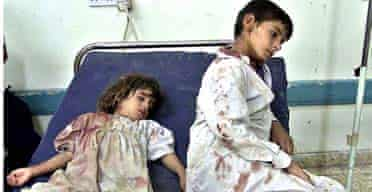 Two Iraqi children, their clothes covered in blood, wait for their wounded parents in a hospital in Falluja