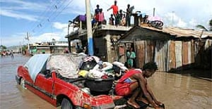 Haitians in Gonaives stay outside their houses after floods and mudslides. Photograph: Ariana Cubillos/AP