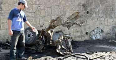 An Iraqi inspects the site where a car bomb exploded in the Iraqi northern city of Mosul