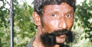 Veerappan stands with a gun in his jungle hideout in 1998. Photograph: AP