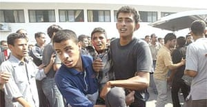 Palestinians carry a wounded boy after he was shot during an Israeli raid at the Khan Younis refugee camp
