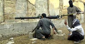 Insurgents load a rocket-propelled grenade into a launch tube during an attack on US forces in Falluja. Photograph: Bilal Hussein/AP