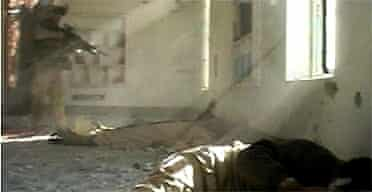A marine points his gun towards a wounded insurgent in a mosque moments before gunfire was heard