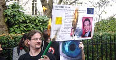 Protesters burn a giant mock ID card with Tony Blair's details on it.