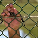 A detainee holds his praying beads while standing outside his cell in Camp Delta at the Guantánamo Bay naval base