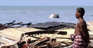 A man surveys tsunami damage off the coast of Lunawa, southern Sri Lanka