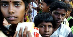 Indian children stand in a queue for relief food in Cuddalore