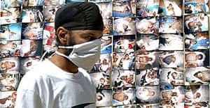 A masked foreigner walks past photos of dead tourists in Thailand