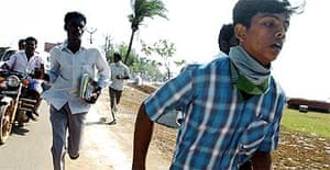 Indian people run for higher ground after hearing of possible further tsunamis