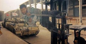 Photograph number nine of a set of 22 showing Lance Corporal Mark Cooley driving a fork lift truck with an Iraqi detainee bound to it