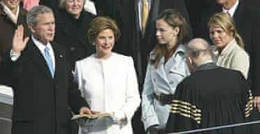 George Bush takes the oath of office from Chief Justice William Rehnquist, right, with first lady Laura Bush, and his daughters Barbara and Jenna at his side