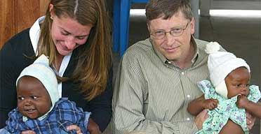 Bill Gates and his wife Melinda cuddle two babies during a visit to Mozambique in 2003