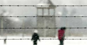 People walk behind barbed wire at Auschwitz-Birkenau on January 27 2005, the 60th anniversary of the camp's liberation