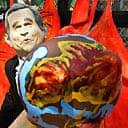A Greenpeace environmental activist wearing a George Bush mask