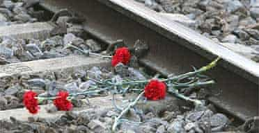 Flowers lie on the railway tracks at El Pozo station in memory of the Madrid train bombing victims