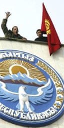 Two protesters with the Kyrgyz state flag on a roof of government headquarters in Bishkek