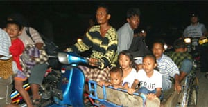 People in Banda Aceh, Indonesia cram onto a scooter and cart as they drive to higher ground following an earthquake