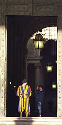 A Swiss guard looks down at the Vatican bronze door entrance