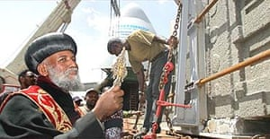 A priest from the Ethiopian Orthodox church blesses a piece of the ancient Axum obelisk as it arrives in Axum 68 years after it was looted by Italian troops