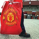 A young Man Utd fan takes home merchandise from Old Trafford. Fans are threatening to boycott club merchandise