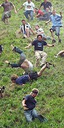 Competitors hurl themselves down a near vertical slope in pursuit of a Double Gloucester cheese