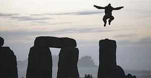 A man jumps in the air from the top of one of the stones as the sun rises over Stonehenge