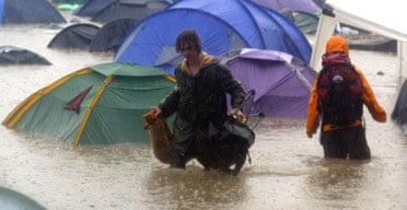 Festival-goers rescue their belongings from their tents during torrential downpours on the first day of the Glastonbury. Photograph: Matt Cardy/Getty Images