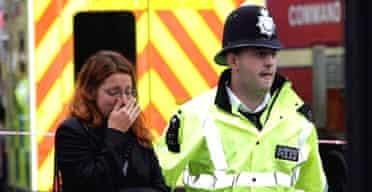 A police officer assists a woman at Edgware Road during the July 7 bombings