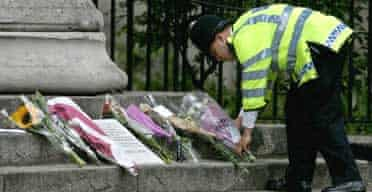 A policeman lays flowers near the scene of yesterday's bomb explosion on board a bus in central London. Photograph: Matt Dunham/AP