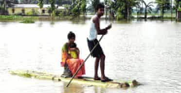 A family move to safety using a makeshift banana tree raft in the north-eastern Indian state of Assam. Photograph: Press Trust of India/AP