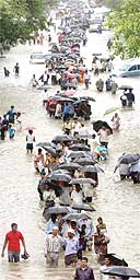 Indians walk down a flooded street after torrential rains paralysed Mumbai