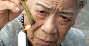 A Japanese woman burns incense to comfort the souls of atomic bomb victims in Nagasaki. Photograph: Yuriko Nakao/Reuters
