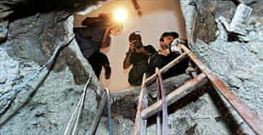 Police and reporters look at the tunnel used by thieves to break into a branch of the Central Bank in the north-eastern city of Fortaleza, Brazil