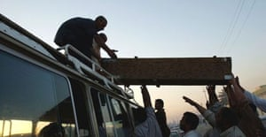 Iraqis load the coffin of a Shia pilgrim killed during yesterday's stampede on to hearse in the Sadr City neighbourhood of Baghdad. Photograph: Wathiq Khuzaie/Getty Images