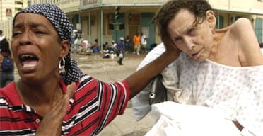A woman outside New Orleans Convention Centre cries for help for an old woman in her care