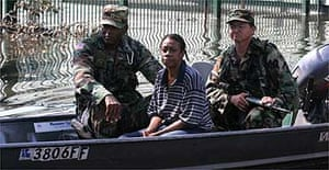 A woman with two California national guard officers after being evacuated from her home in New Orleans