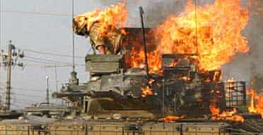 A British soldier prepares to jump from a burning tank which was set ablaze after a shooting incident in the southern Iraqi city of Basra