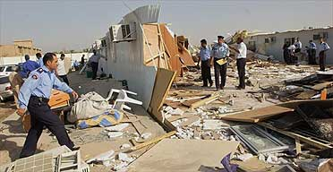 Iraqi policemen walk through debris at the central jail in Basra