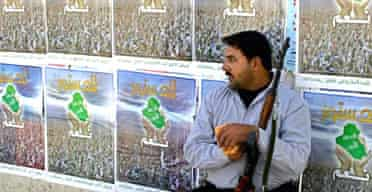 An Iraqi policeman stands in front of posters campaigning for a Yes vote in this month's referendum . Photograph: Qassim Zein/AFP/Getty Images