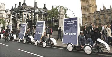 Campaign posters for Conservative leadership challenger Kenneth Clarke are seen aboard recumbent bicycles as they pass Big Ben