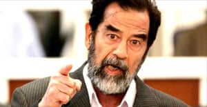 Saddam Hussein defiantly speaks to the presiding judge Rizgur Ameen Hana Al-Saedi as his trial begins in a heavily fortified courthouse in Baghdad's green zone. Photograph: Bob Strong/AFP/Getty