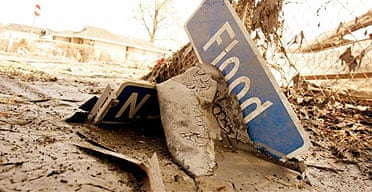 The street sign for Flood Street sits in the mud where it fell after Hurricane Katrina in New Orleans, Louisiana