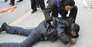 A man helps a demonstrator lying on the ground during an opppositin protest in Baku, Azerbaijan