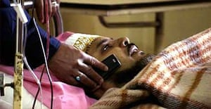 A nurse holds a phone for a wounded British national at Yarmouk hospital
