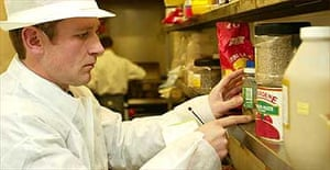 An environmental health officer inspects the kitchen of a restaurant