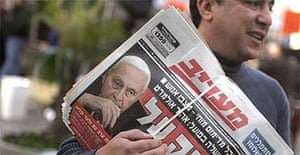 A man delivers morning papers showing the Israeli prime minister, Ariel Sharon