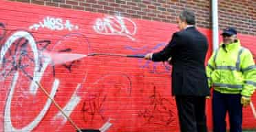 Tony Blair cleans graffiti from a wall with a high-pressure hose during a visit to Toothill community centre in Swindon. Photograph: Adrian Dennis/AFP/PA
